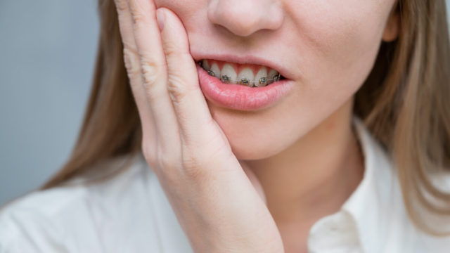 painful_braces_pain: lady with braces holding cheek in pain